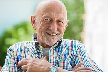 elderly man sitting and smiling