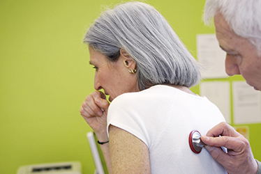 elderly female patient coughing as doctor examines her back with a stethoscope