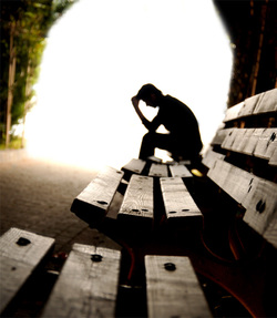 backlit picture of a man sitting on a bench with his hand on his head, only seeing the outline of his body