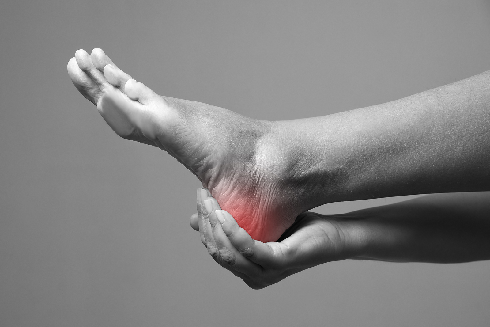 black and white image of a woman holding her heel, which is glowing red from pain