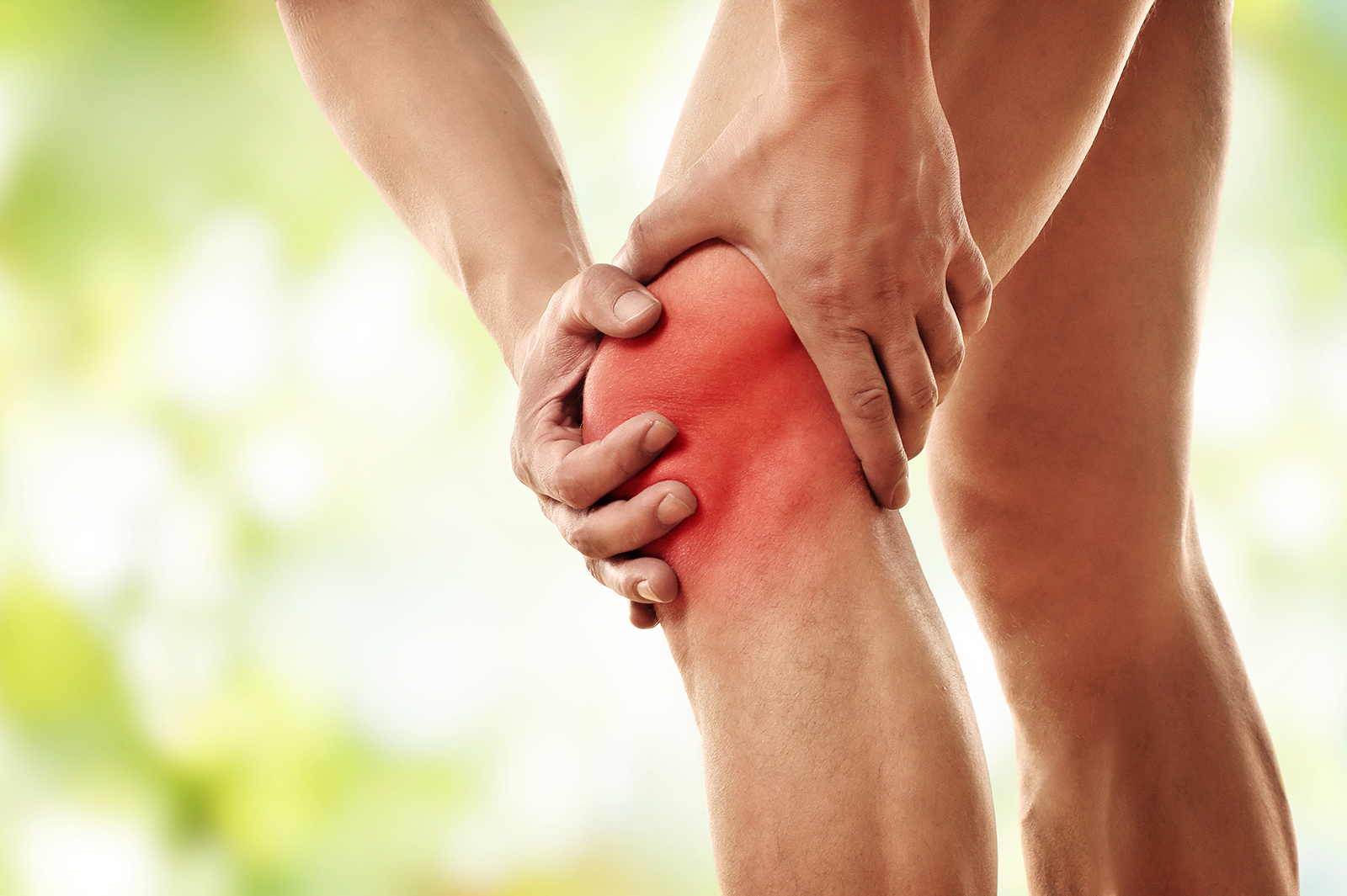 close up of man in pain holding knee that is bright red with both hands