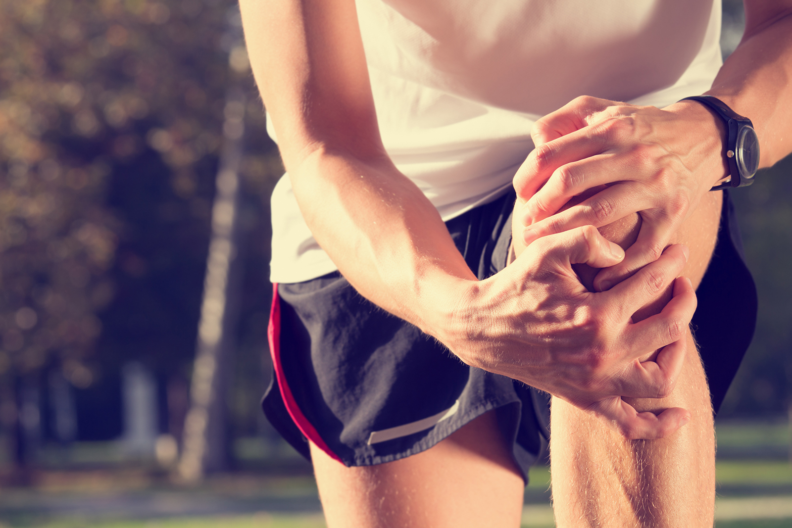 male runner holding knee with both hands