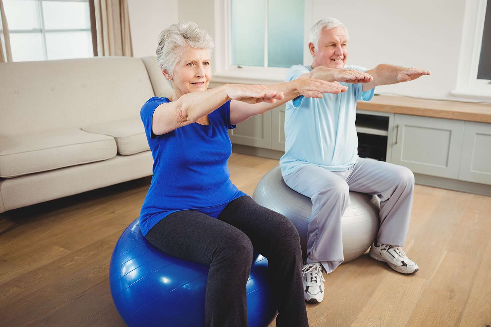 Senior couple exercising on exercise ball