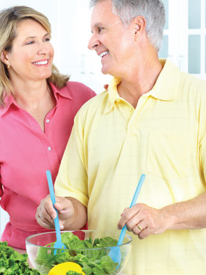 couple making salad and smiling at each other